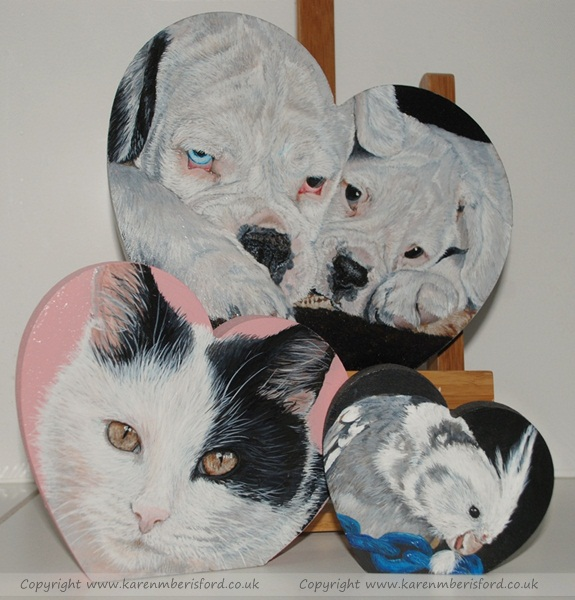traditional hearts paintings by Karen M Berisford depicting a black and white shorthaired cat, a white faced cockatiel and 2 white boxer dogs on MDF hearts
