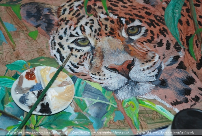 Acrylic paints in a small porcelain palette over an Acrylic painting of a Jaguar in progress