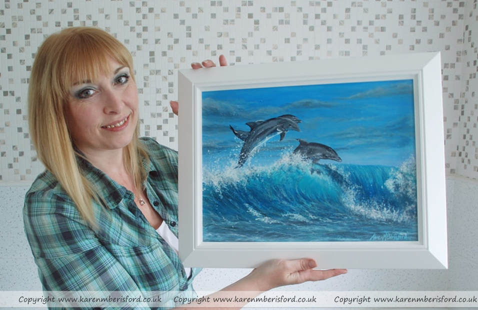Artist Karen M Berisford holding the acrylic portrait of a Trio of jumping Dolphins framed in the Bakewell frame